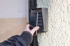 人打开与巧妙的电话的门 库存图片