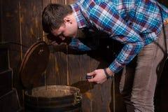 年轻人打开了桶和设法解决难题得到 库存照片