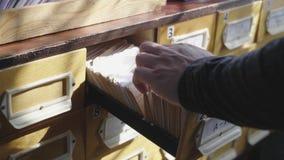 人打开数据库抽屉 年轻图书管理员打开图书证索引 档案,数据库,图书馆概念 影视素材