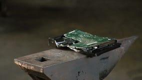 人打破与爬犁重的锤子的硬盘,在铁砧 慢动作特写镜头有声音 股票录像