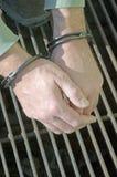 人扣上手铐的刑警 免版税库存照片
