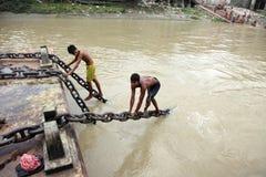 年轻人执行在一条移动的小船的特技 库存图片