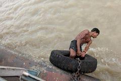 年轻人执行在一条移动的小船的特技 库存照片