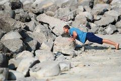 年轻人执行在石头中的俯卧撑 免版税库存照片