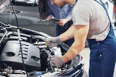 人技工和妇女顾客看汽车敞篷并且谈论修理 库存照片