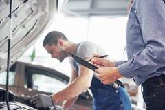 人技工和妇女顾客看汽车敞篷并且谈论修理 免版税库存图片