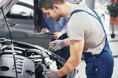 人技工和妇女顾客看汽车敞篷并且谈论修理 库存图片