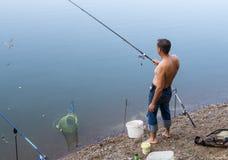 人抓在结尾杆的鱼,在湖的岸 免版税库存照片