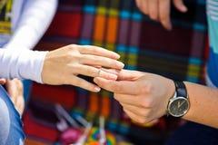 人投入妇女定婚戒指在野餐在背景 免版税库存图片
