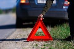 人投入红色警告三角 图库摄影