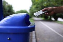 人投掷在垃圾的电话 免版税库存照片