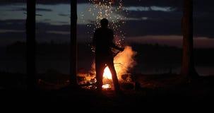 人投掷并且改进已经烧与明亮的火焰在晚上的火 股票录像