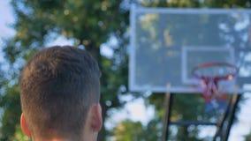 人投掷的篮球到箍和击中和审阅圆环的今后走,球里,使用在公园 股票视频