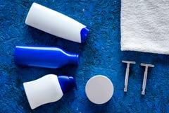 人护发和刮的` s化妆用品 香波,胶凝体,剃刀,在蓝色背景顶视图copyspace的蜡 免版税库存图片