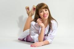 年轻人护理与说谎在她的腹部的听诊器 库存照片