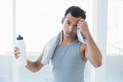 年轻人抹冒汗了与毛巾在健身演播室 库存图片