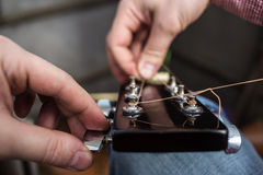 人拉扯新的在特写镜头的吉他串声学吉他 库存图片