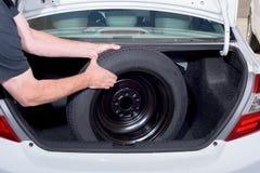 人拉扯从汽车后车箱的备用轮胎  免版税库存图片