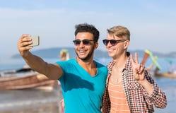 人拍在长尾巴小船前面的游人夫妇Selfie照片在细胞巧妙的电话,愉快两个年轻的人的海滩 图库摄影