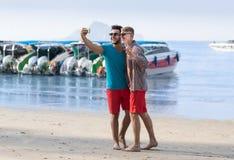人拍在长尾巴小船前面的游人夫妇Selfie照片在细胞巧妙的电话,愉快两个年轻的人的海滩 库存照片