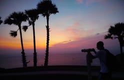 人拍照片在日落的海滩 图库摄影