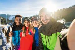 人拍Selfie照片的滑雪雪板手段冬天雪山愉快的微笑的朋友 库存照片