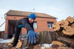 人拔出从木堆的一本日志 免版税库存照片