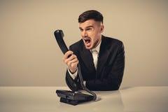 年轻人拨电话号码,当坐在办公室时 图库摄影