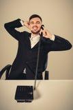 年轻人拨电话号码,当坐在办公室时 免版税库存图片