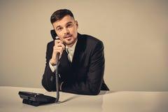 年轻人拨电话号码,当坐在办公室时 库存图片