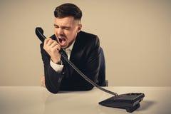 年轻人拨电话号码,当坐在办公室时 库存照片