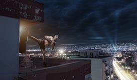 年轻人拳击训练,在城市上的房子顶部 库存照片