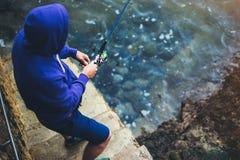 人拿着一根钓鱼竿并且抓在自然的鱼在海背景,渔夫在蓝色oc上度过假期的行家 库存照片