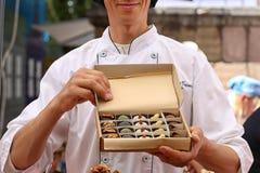 人拿着一箱美丽的手工制造糖果 免版税图库摄影