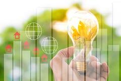 人拿着与太阳的电灯泡自白天,与bokeh背景和统计想法工作的图表使用墙纸或背景 免版税库存照片