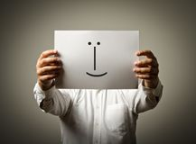 人拿着与微笑的白皮书 说谎者概念 免版税库存图片