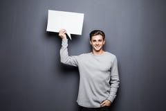 年轻人拿着与空间的微笑人白色空白的讲话泡影在灰色背景隔绝的文本的 库存图片