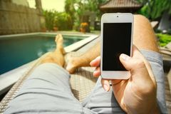 人拿着他的有黑屏的智能手机在他的在水池的背景的手和他的在deckchair的脚 免版税库存照片