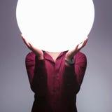人拿着光大球形在他的面孔的 免版税库存图片