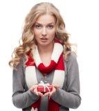 年轻人拿着圣诞节礼物的惊奇的妇女 免版税库存照片