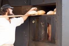 人拿着在大面包面包的铁锹 免版税库存照片