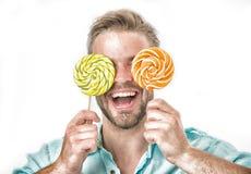 人拿着在眼睛的大棒棒糖作为镜片 有刺毛的人喜欢甜点 爱吃甜品的胃口概念 微笑的面孔的人 图库摄影