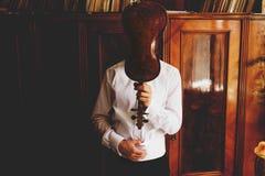 人拿着在他的面孔前面的一把小提琴  免版税库存图片