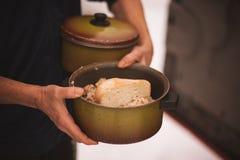 人拿着平底锅用免费食物 免版税库存图片
