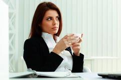 年轻人拿着杯子的惊奇的女实业家 免版税库存照片