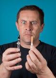 人拿着电和普通的香烟 免版税库存照片
