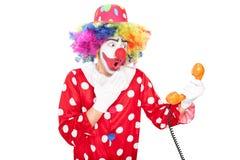 年轻人拿着电话报告人的惊奇的小丑 免版税图库摄影