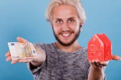 人拿着金钱和房子piggybank 免版税图库摄影