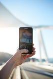 人持有桥梁的一个电话和被拍摄的观点 免版税库存照片