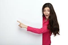 年轻人指向一个空白的委员会的微笑妇女 免版税库存图片